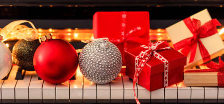 Chritmas balls and gift boxes on classical piano keyboard, front view