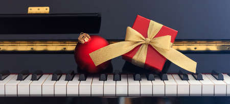 Red Chritmas ball and gift box with golden bow on classical piano keyboard, front view Stock Photo