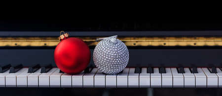 Red Chritmas balls on classical piano keyboard, front view