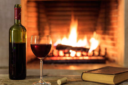 Red wine and a book on a wooden table, blur burning fireplace background