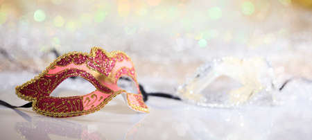 Pink carnival mask on white surface, abstract bokeh background Stock Photo