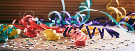 Carnival party concept. Colorful confetti and serpentines on wooden background