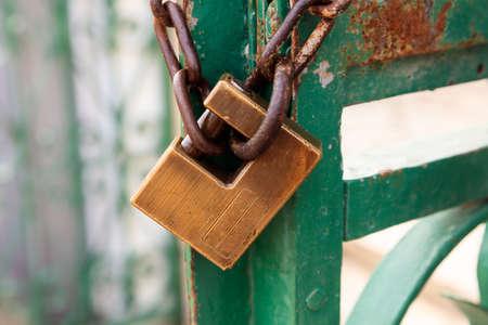 Old rusty padlock blocking the metal entrance. Close up view.