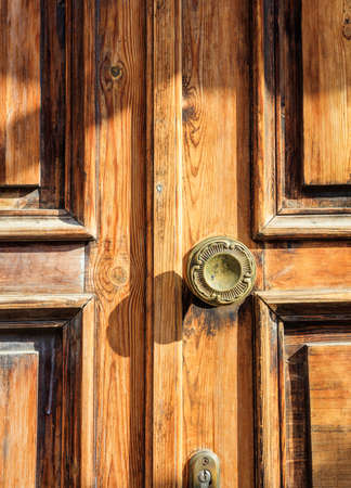 Closeup view of an old wooden door handle with flower details. Stock Photo