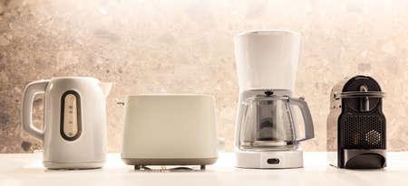 Modern kitchen appliances placed on white surface. Colorful, blurred backdrop. Closeup view, detail. Foto de archivo