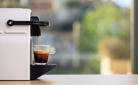Making espresso. Espresso coffee maker on a wooden table. Blurred background, space for text, front view