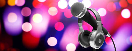 Live music concert concept. Cable microphone and headphones on stand on bokeh background, banner. 3d illustration