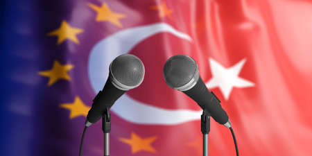 Relationship between European Union and Turkey. Two cable microphones in front of blurred flags for backdrop. 3d illustration 写真素材