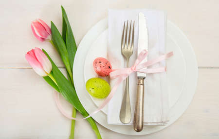 Easter table setting with pink tulips on white wooden background. Top view Stock Photo - 95631295