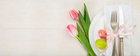 Easter table setting with pink tulips on white wooden background. Top view, banner, space for text 스톡 콘텐츠