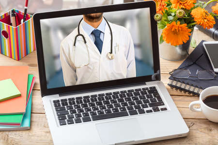 Telemedicine concept. Doctor GP on a computer screen, office desk background Stockfoto