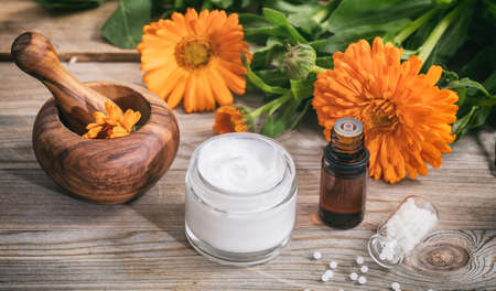 Calendula alternative medicine. Essential oil, ointment a mortar and white pills on a wooden table, fresh blooming calendula background,