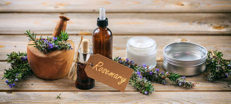 Rosemary aromatherapy. Essential oil and cosmetics, fresh blooming twig in a mortar, tag with text rosemary, banner. Wooden table background