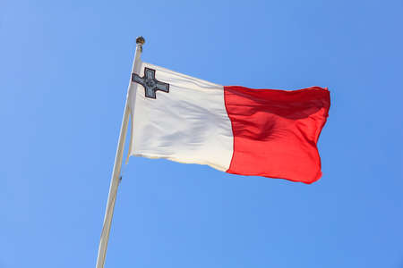 Malta flag. Malta flag on a flagpole waving on a bright blue sky background 免版税图像