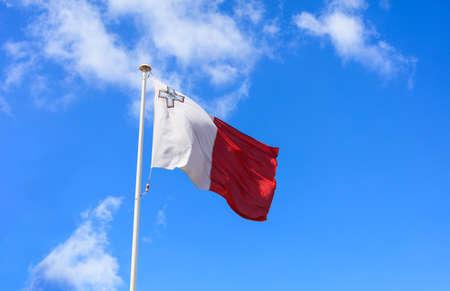 Malta flag. Malta flag on a flagpole waving on a bright blue sky background Stok Fotoğraf
