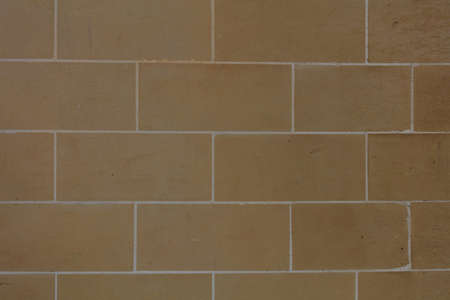 Brown stone wall facade background in Malta, closeup view