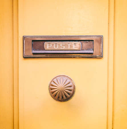 Old brass mail letter box and door knob on a yellow front door, text poste