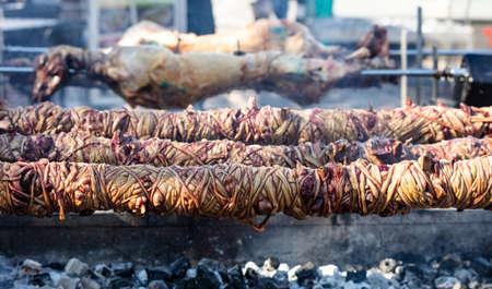 Whole kokorec and lamp spits on coals fire. Greek Easter, Monastiraki, Athens Greece