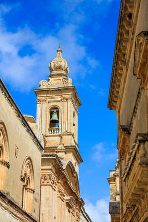 Mdina, Malta island. Narrow street wth church belfry and buildings stone facades on blue sky background