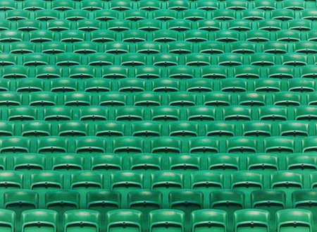 Rows of green empty folding stadium seats background
