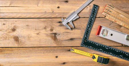 Carpentry tools. Measure tape, spirit level and rulers on wooden background, copy space, top view
