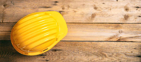 Construction site safety. Yellow protective hard hat on wooden background, copy space, top view