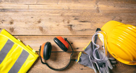 Construction site safety. Protective hard hat, headphones, gloves and glasses on wooden background, copy space, top view 免版税图像