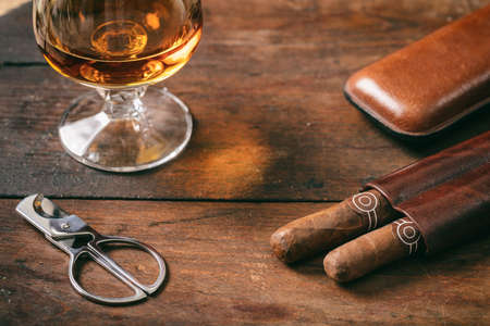 Cuban cigars and a glass of cognac brandy on wooden background, closeup view with details 免版税图像