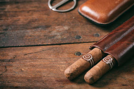 Cuban cigars in a leather case on wooden background, copy space