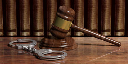 Metal police handcuffs and judge gavel on wooden desk, law books background. 3d illustration