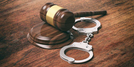 Metal police handcuffs and judge gavel on wooden background, 3d illustration