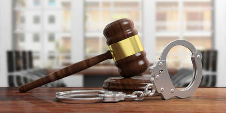 Metal police handcuffs and judge gavel on wooden desk, blur office background. 3d illustration Stock Photo