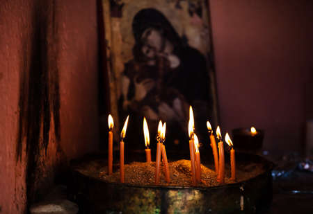 Sacred ritual concept. Prayer candles on a candlestick with sand, blurry image of an icon of the Virgin with child in the background.
