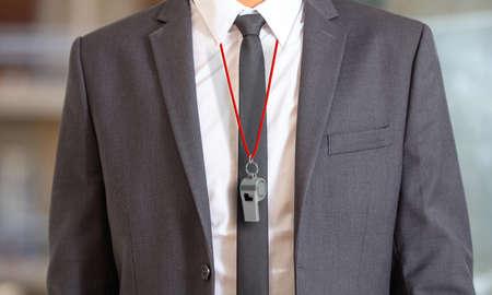 Sportzaken. Man in pak met een fluitje met rode koord. 3D-afbeelding