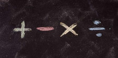 Concepto matemático. Símbolos matemáticos básicos escritos con tizas de colores, aislado sobre fondo de pizarra
