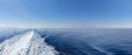 Mediterranean sea. Boat white wake, prop wash foam on blue sea and sky background, view from the ship. Copy space, banner