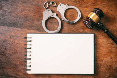 Law and order concept. Handcuffs, gavel and a notebook on a wooden background with copy space.