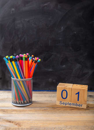 Back to school. September 1st date and colorful pencils on blackboard background, space for text