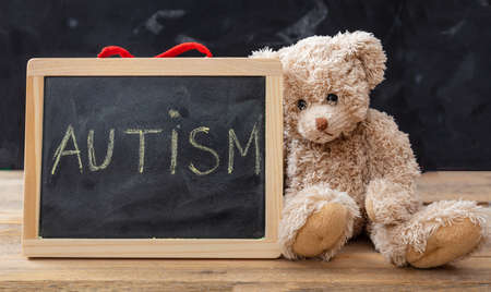 Autism and school. Teddy bear and a blackboard. Autism text drawing on the blackboard