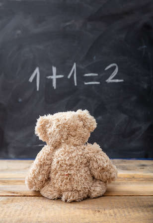 School class math. Teddy bear looking at a simple equation on a blackboard.  One plus one equals two