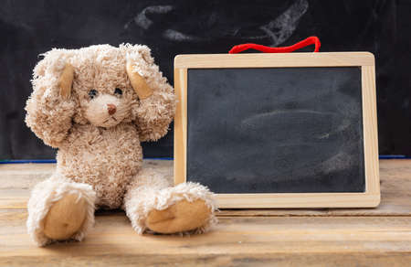 Bullying at school or learning difficulties concept. Teddy bear covering ears and a blank blackboard, space for text Stockfoto