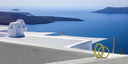 Wedding in a greek island concept. Wedding rings on a whitewashed wall, Santorini volcano view background