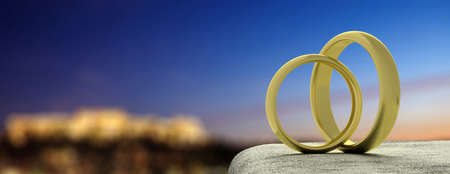 Golden wedding rings on a white roof, city lights and sky background, banner, copy space