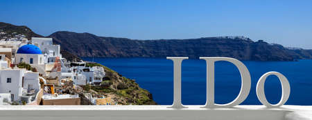 Wedding in Santorini, Greece concept. I DO text on Fira general view background, banner. Stock Photo