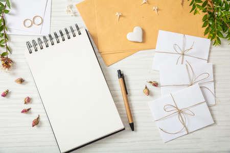 Hochzeitseinladungsvorbereitung. Flache Lage und Draufsicht auf Aufgabenliste und Hochzeitseinladungen auf einer weißen hölzernen Tischplatte, Kopienraum.