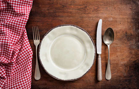 Rustic place setting. Traditional cutlery and plate, red checkered tablecloth on wooden table, top view
