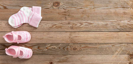Baby girl shower concept on wooden background, copy space, top view