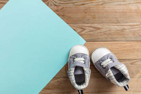 Baby boy shoes, shower invitation concept on pastel blue and wooden background, copy space, top view Reklamní fotografie