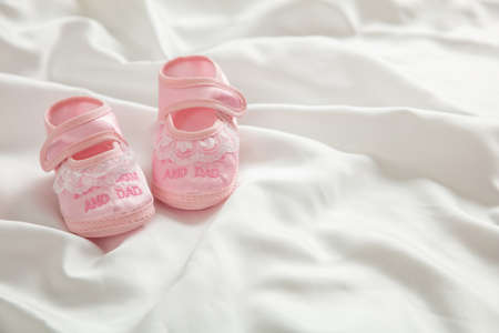 Baby girl shoes, shower invitation concept on white satin, copy space Reklamní fotografie