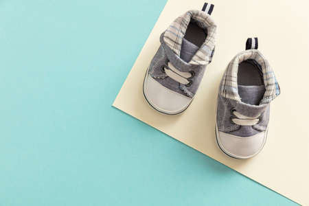Baby boy shoes, shower invitation concept on pastel colors background, copy space, top view